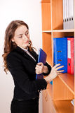 Kobieta bierze czerwoną falcówkę od półki zdjęcie royalty free