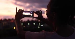 Kobieta bierze fotografię zmierzchu niebo zdjęcie wideo