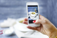 Kobieta bierze fotografię rybia polewka z smartphone Zdjęcie Royalty Free