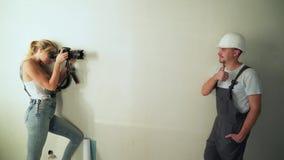 Kobieta bierze fotografie pracownik odnawi mieszkanie przy budową zbiory wideo
