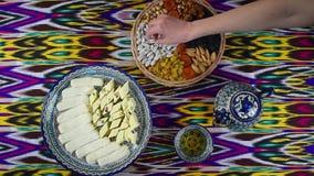 Kobieta bierze niektóre orientalnych cukierki od stołu w kawiarni, odgórny widok, Bukhara zbiory