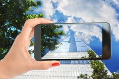 Kobieta bierze obrazek wysoki drapacz chmur w Manhattan Nowy Jork z niebieskim niebem i chmurami Fotografia Stock