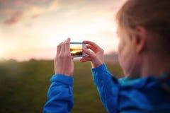 Kobieta bierze obrazki z jej smartphone Obrazy Royalty Free
