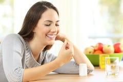Kobieta bierze omedze 3 witaminy pigułki Obrazy Stock