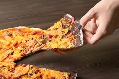 Kobieta bierze plasterek czarny i biały pizza na drewnianym stole zdjęcie stock