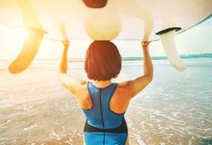 Kobieta bierze surfboard na głowie i iść w ocean fala zdjęcia stock
