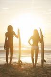 Kobieta bikini surfingowa Surfboards & dziewczyn zmierzchu plaża Zdjęcie Stock