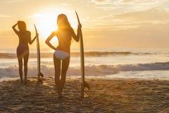 Kobieta bikini surfingowiec & Surfboard zmierzchu plaża Obraz Royalty Free