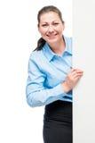 Kobieta bizneswomanu zerkanie out od dużego plakata za Fotografia Royalty Free
