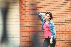 Kobieta blisko ściana z cegieł Obraz Royalty Free