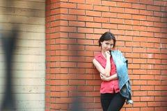 Kobieta blisko ściana z cegieł Zdjęcie Stock