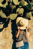 Kobieta blisko kamiennego ogrodzenia z kaktusami zdjęcie royalty free