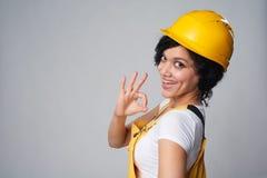 Kobieta budowniczy jest ubranym żółtego gacenie hełm i kombinezon pokazuje OK Obraz Stock