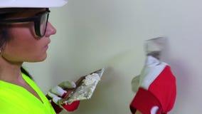 Kobieta budowniczy z szpachelki pełnią mała dziura na ścianie zbiory