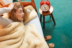 Kobieta budzi się up opóźnionego obracający daleko budzika Zdjęcia Stock