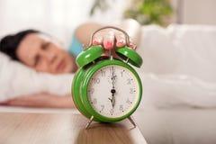 Kobieta budzi się w łóżku, w górę ranku obraca daleko budzika póżno wewnątrz Zdjęcia Stock