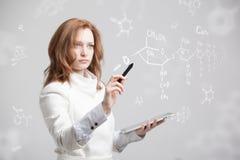 Kobieta chemik pracuje z chemicznymi formułami na popielatym tle zdjęcie royalty free
