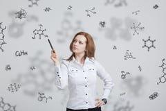 Kobieta chemik pracuje z chemicznymi formułami na popielatym tle zdjęcia stock