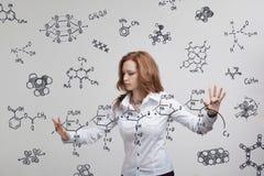 Kobieta chemik pracuje z chemicznymi formułami na popielatym tle fotografia royalty free