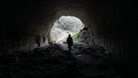 Kobieta chodząca od antycznego przejścia podziemnego w Nysa out, Sultanhisar, Turcja koniec tunelu światła 4K zbiory