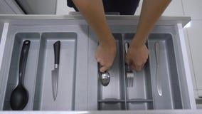 Kobieta chodzi kuchenna spiżarnia i bierze rozwidlenie od kreślarza i łyżkę W pudełkowatych tylko dwa rozwidleniach i łyżkach zbiory