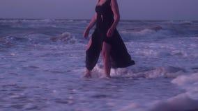 Kobieta chodzi na silnych falach z pianą, brzeg, morze, piasek, lato, wieczór zbiory wideo
