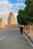 Kobieta chodzi Wielki meczet w Kairouan w czerni ubraniach, Tunezja Zdjęcia Stock