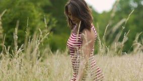 Kobieta chodzi wzruszające uprawy na polach z jej ręką, piękny żeński uśmiechu spacer zdjęcie wideo