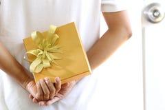 Kobieta chuje złocistego prezenta pudełko Obrazy Royalty Free