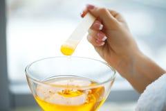 Kobieta chwyta parafinowego wosku pomarańczowy puchar Kobieta w piękno salonie zdjęcie royalty free