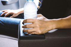 Kobieta chwyta wody pitnej butelka na filiżanka właścicielach Zdjęcia Royalty Free