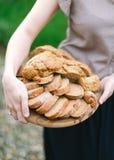 Kobieta chwyty wewnątrz wręczają drewnianą tacę z rżniętym chlebem Fotografia Royalty Free
