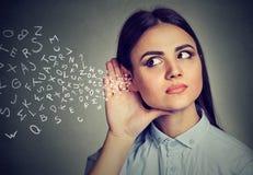 Kobieta chwyty wręczają blisko ucho i słuchają ostrożnie abecadło listy lata wewnątrz zdjęcia royalty free