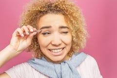 Kobieta ciągnie ot włosy od jej brwi używać pincetę dla to Ja jest bolesny Doesn ` t lubi je Odizolowywający dalej Obraz Stock