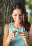 Kobieta ciągnie płatki z kwiatu główkowania: kocha ja, on Obraz Royalty Free