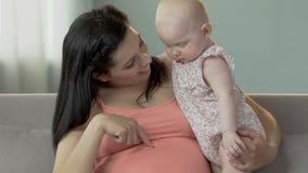 Kobieta ciężarna z dziecka mienia niemowlakiem, wskazuje znosić, dziecko patrzeje w dół zbiory