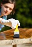Kobieta cieśla sprawdza świeżo malującego drewno Fotografia Stock