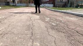 Kobieta cieki w butach są na asfalcie wśród jesień liści Kroki na drodze zbiory wideo