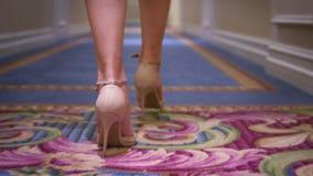Kobieta cieki w wysokości heeled buty chodzi na dywanowej podłoga plecy widoku zbiory