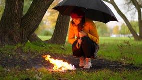 Kobieta ciepła ogieniem w zimnym deszczowym dniu pod parasolem, ciemny jesień las zbiory wideo