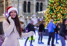 Kobieta cieszy się świątecznego sezon na Bożenarodzeniowym targowym lodowym lodowisku obrazy stock