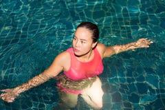 Kobieta cieszy się bawić się jej piłkę w pływackim basenie przy nocą w hotelu Zdjęcia Stock