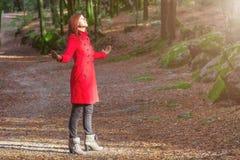 Kobieta cieszy się ciepło zimy światło słoneczne samotnie na lasu parka ścieżce z rękami otwiera obrazy stock