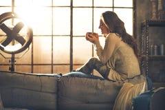Kobieta cieszy się filiżankę gorący napój w mieszkaniu zdjęcie stock