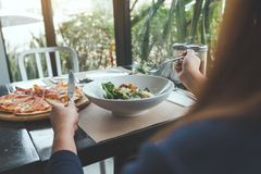 Kobieta cieszy się jedzący Caesar pizzy w restauraci i sałatki fotografia royalty free