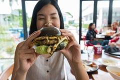 Kobieta cieszy się jedzący tylnego hamburger Obrazy Royalty Free