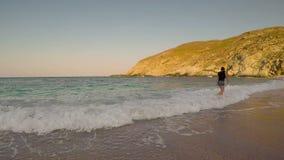 Kobieta cieszy się jej wakacje przy Zorkos plażą w Andros bawić się z fala zbiory