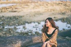Kobieta cieszy si? obsiadanie na skale seashore zdjęcia royalty free