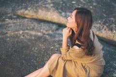 Kobieta cieszy si? obsiadanie na skale seashore zdjęcie stock