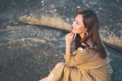 Kobieta cieszy si? obsiadanie na skale seashore zdjęcia stock